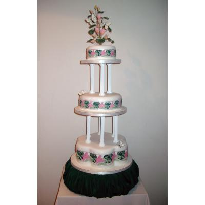 Tall Pillars seperate the Tiers of this Highly Decorated Wedding Cake
