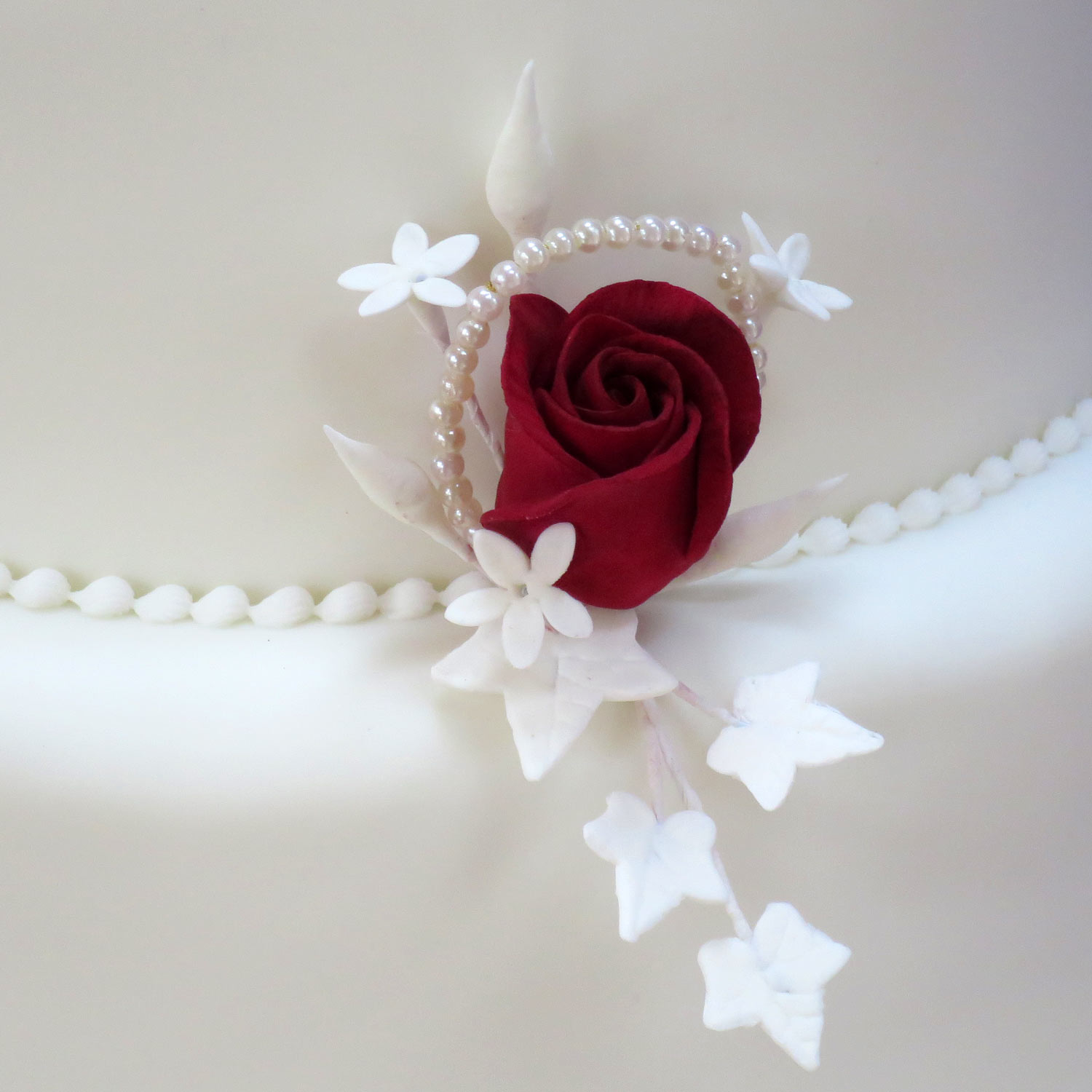 Burgundy sugar rose with jasmine, ivy and pearls.