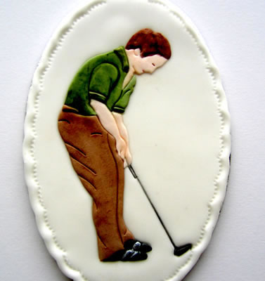 Sugarcraft plaque decorated with a Patchwork Cutter Golfer